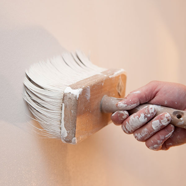 Maler streicht eine Wand mit einem Quast