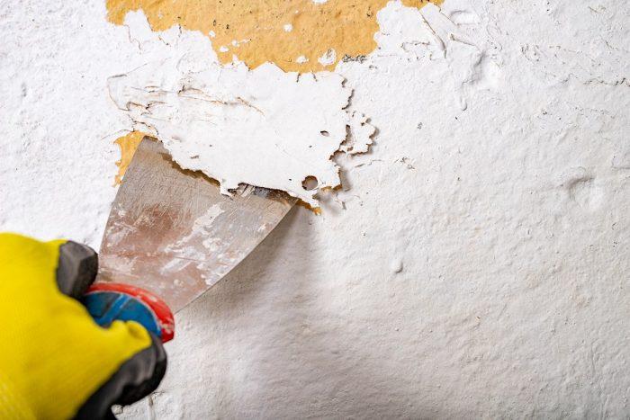 Alte Wandfarbe wird mit einem Spachtel entfernt