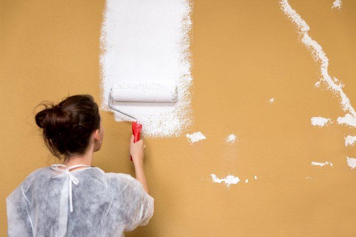 Frau streicht eine braune Wand weiß