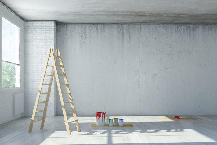 Betonwand mit Leiter und Farbeimern davor