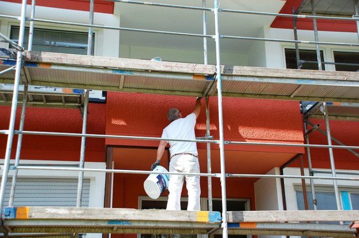 Maler steht auf einem Gerüst und streicht die Hausfassade