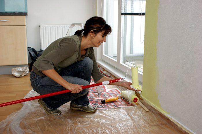 Junge Frau malert eine Wand in der Küche.