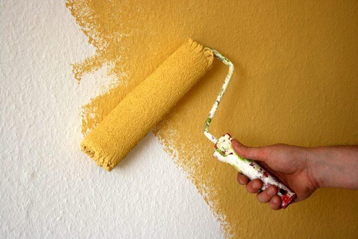 Tapete wird mit Farbrolle gelb gestrichen