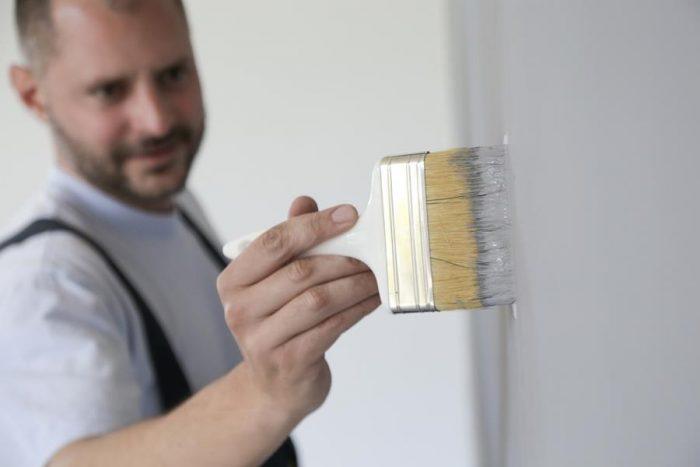 Anstreicher streicht Wand weiß