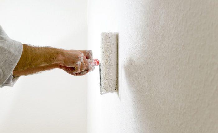 Wand wird mit Farbrolle weiß gestrichen