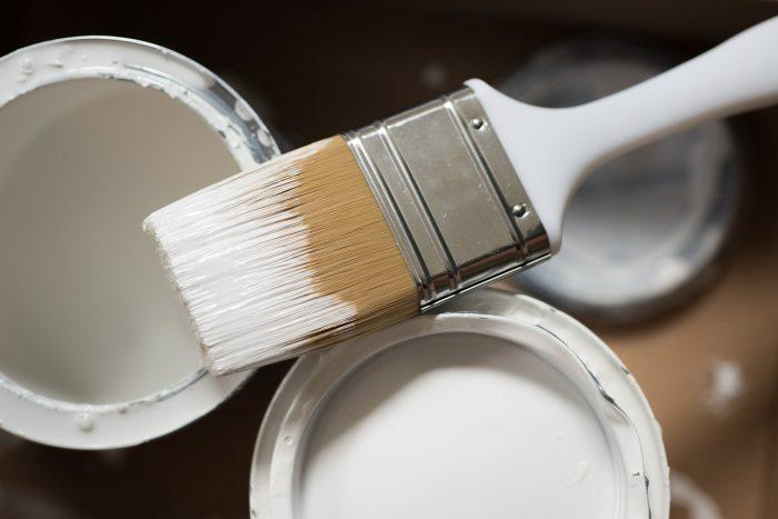 Pinsel liegt auf 2 weißen Farbtöpfen
