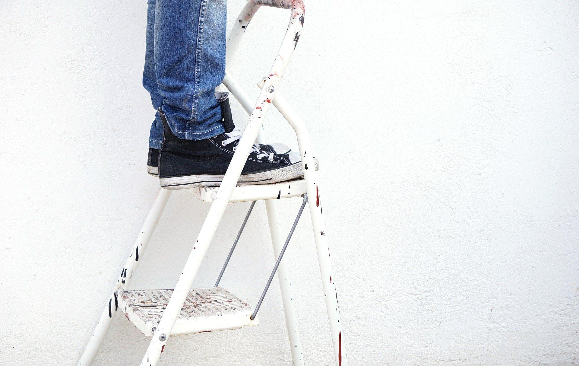 Person mit Jeans und schwarzen Turnschuhen steht auf einer Leiter und streicht
